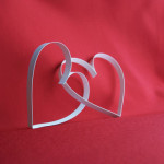 deux coeurs entrelacés, sur fond rouge