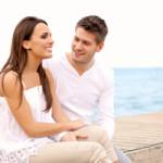 jeune couple souriant qui communique entre eux au bord de l'eau