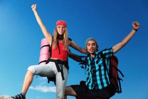 Couple de jeunes gens sortant vainqueur d'une escapade au sommet d'une montagne.  Leurs visages expressifs et leur bras levés vers le haut dénotent la fierté de leur succès