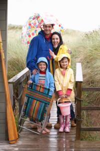 une famille avec 2 enfants sourient malgré le tempps pluvieux qui aurait dû gâcher leur promenade au bord du lac